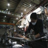 Japan factory output flat in July, weak demand clouds outlook